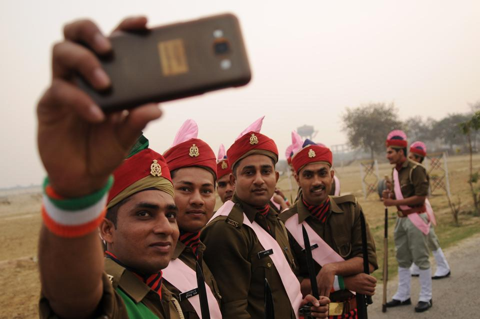 Uttar Pradesh Armed Police personnel click a  selfie before taking part in the parade. (Burhaan Kinu/HT PHOTO)