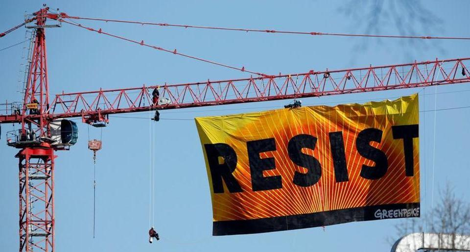 Greenpeace activists hold an anti-Trump protest as they display a banner reading 'Resist' from a construction crane near the White House in Washington, U.S., January 25, 2017.