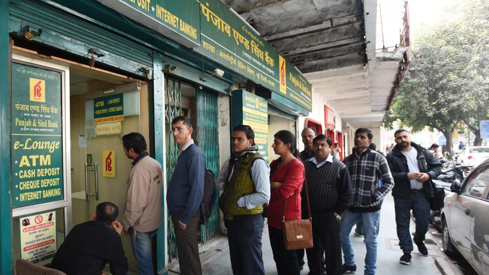 People queue up outside Punjab and Sind Bank ATM to withdraw cash near Connaught Place in New Delhi.