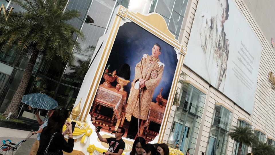 People walk past a portrait of Thailand's King Maha Vajiralongkorn Bodindradebayavarangkun and the late King Bhumibol Adulyadej at a department store in central Bangkok, Thailand, January 17, 2017.  A gang of con-artists including a monk were arrested by police for running a racket asking people to pay money for royal individuals to attend their weddings.