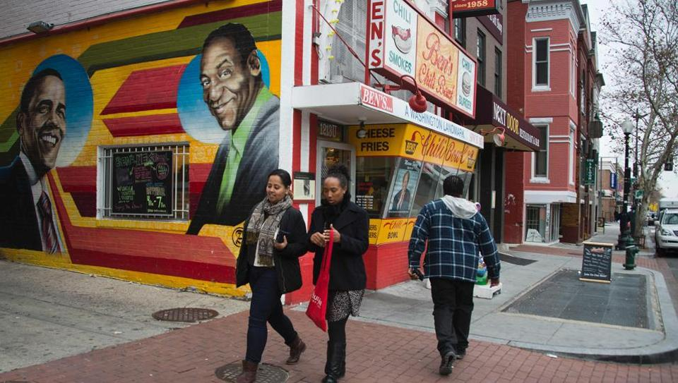 People walk past a mural of former US President Barack Obama and comedian Bill Cosby painted on the side of Ben's Chili Bowl in Washington, DC.