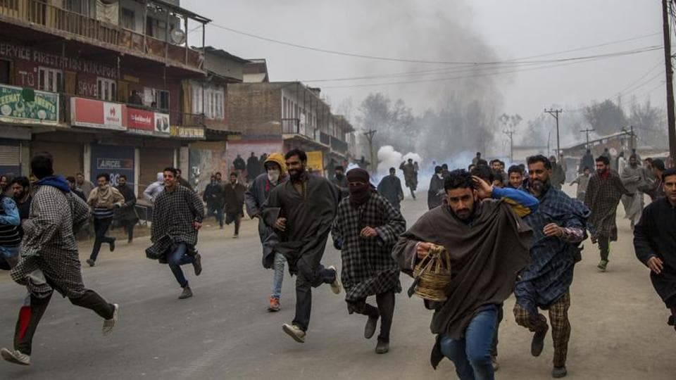 People run for cover from tear gas shells and pellets fired at them during a protest in Kakpora village, south of Srinagar.