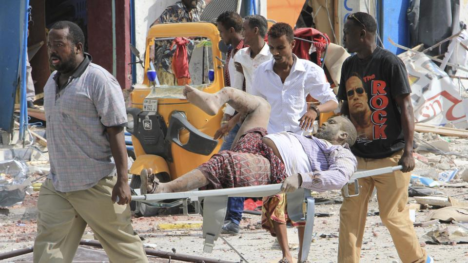 Somali men carry a civilian who was wounded in a suicide car bomb attack on a hotel in Mogadishu, Somalia.\