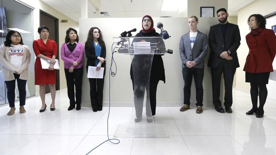 Alia Salem, center, executive director of the Dallas/Fort Worth chapter of the Council on American-Islamic Relations, leads a news conference with community activists concerning recent executive orders by President Donald Trump, Thursday, Jan. 26, 2017, in Dallas.