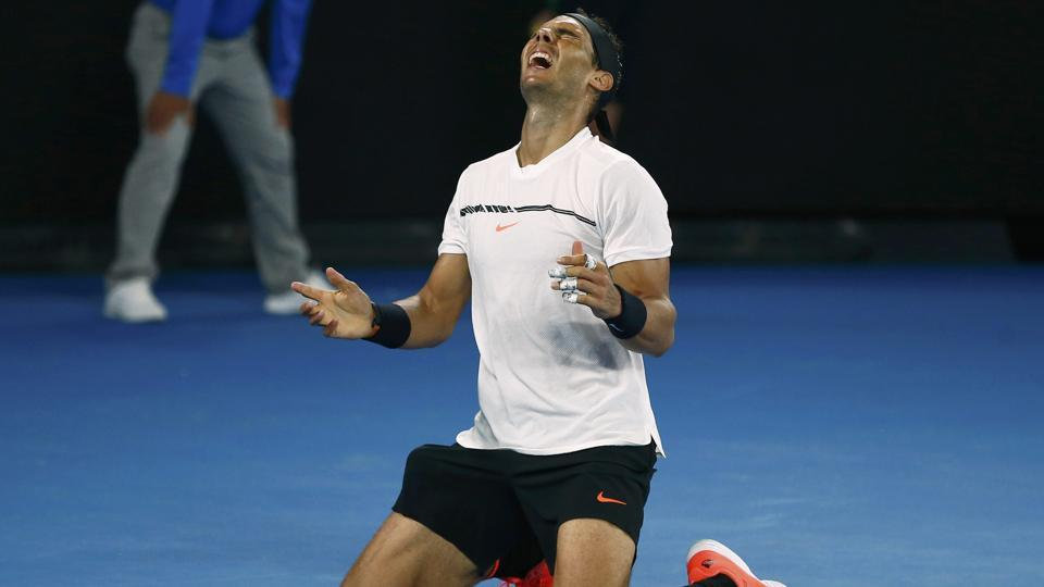 Rafael Nadal falls onto the court as he celebrates winning his Men's singles semi-final match. (REUTERS)
