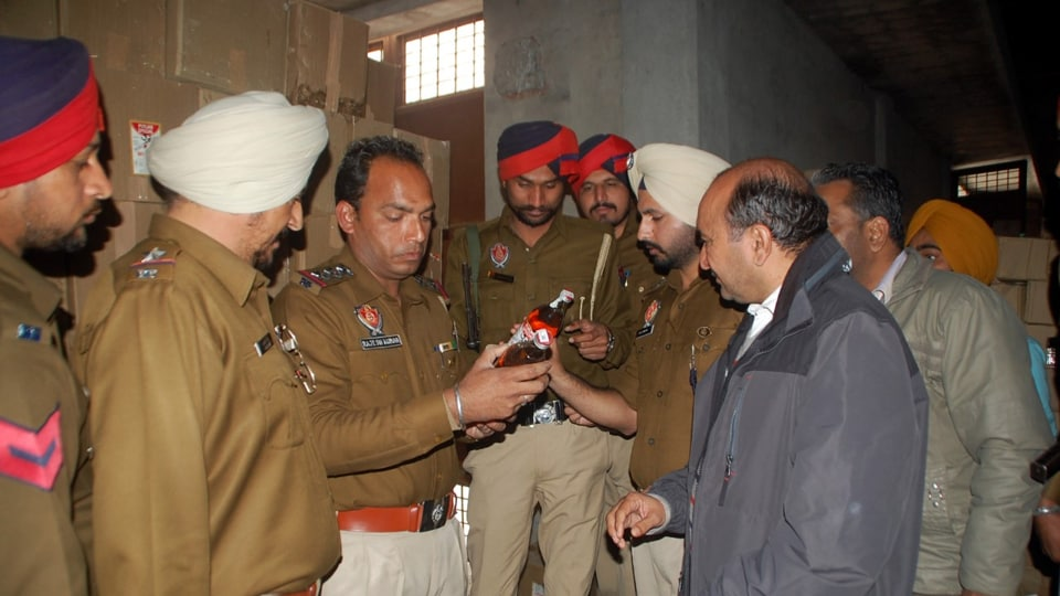 Punjab police cops checking a bottle of illicit liquor recovered from a godown in Bathinda on Saturday.