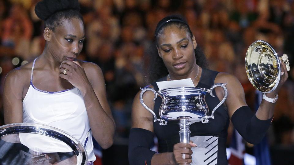 Serena Williams (right) takes the lid off her trophy as sister Venus watches. (AP)