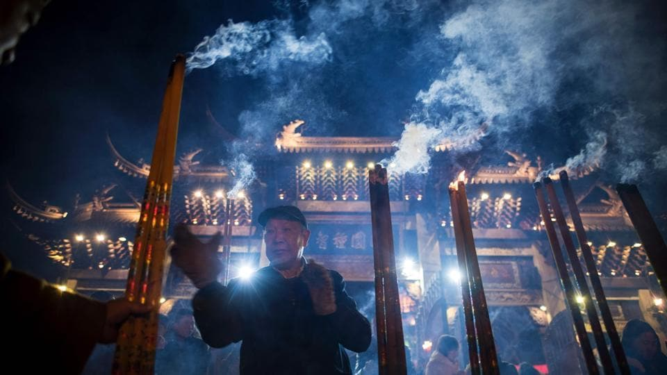 A man prays with incense sticks at the Longhua temple in Shanghai. (Johannes Eisele/AFP)
