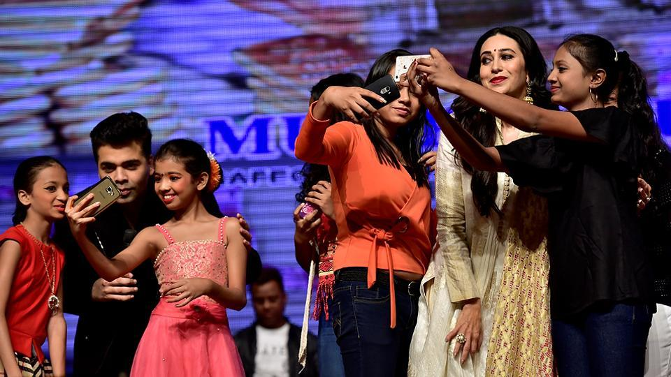 Karan Johar and Karisma Kapoor  pose for selfies with children at the function. (Arijit Sen/HT PHOTO)