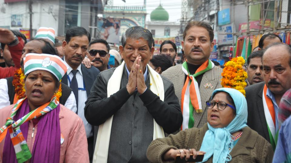 Chief minister Harish Rawat greets people during a road show in Dehradun on Saturday.
