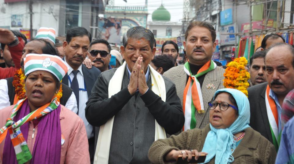 Chief minister Harish Rawat greets people during a road show in Dehradun on Saturday.