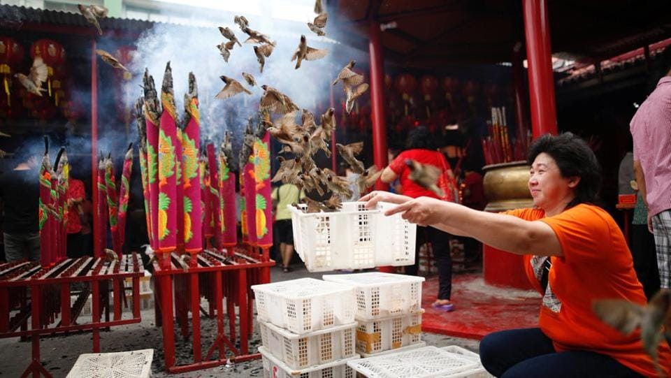 A woman releases birds for good luck during Lunar New Year celebrations at Dharma Bhakti temple in Jakarta, Indonesia. (Darren Whiteside/REUTERS)