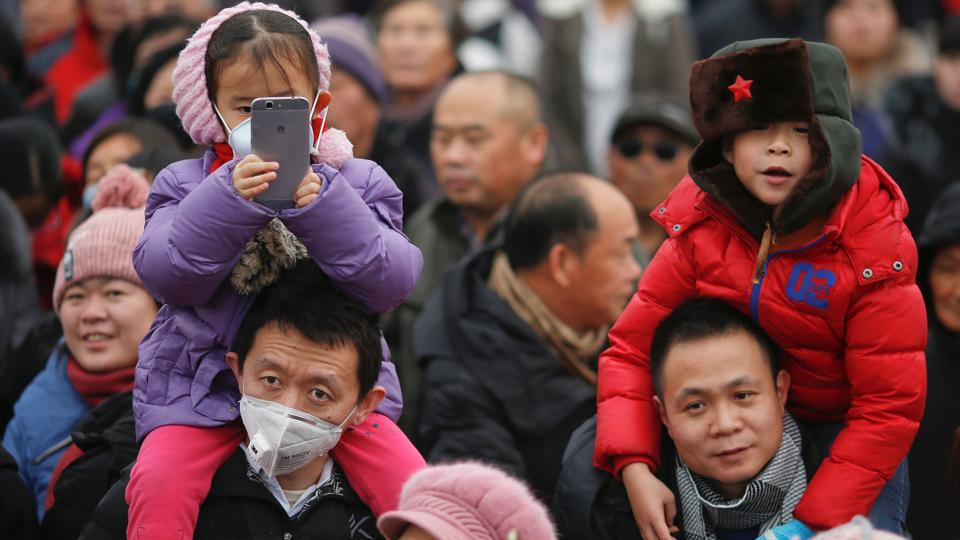 People, some wearing face mask against pollution, follow performers during a re-enactment of an ancient Qing Dynasty ceremony as the Lunar New Year of the Rooster is celebrated at the temple fair at Ditan Park (the Temple of Earth), in Beijing, China. (Damir Sagolj/REUTERS)