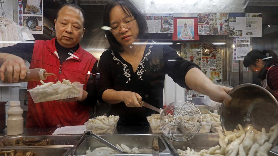 "In this Monday, Jan. 23, 2017 photo, chicken feet snacks shop owner Leung Kin-kung, left, and his wife Leung pack chicken feet takeaway for customer in Hong Kong. Saturday marks the start of the lunar Year of the Rooster and families in China will reunite for festivities, fireworks and food. While tradition calls for feasting on ""auspicious"" foods, many will also munch on staple snacks like phoenix claws, the Chinese name for chicken feet. (Vincent Yu/AP)"