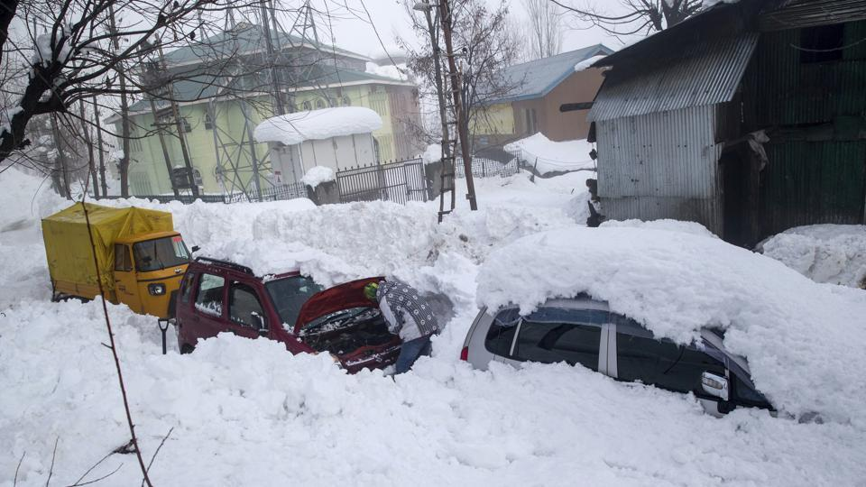 A Kashmiri man checks his vehicle stuck in snow in Tangmarg, about 41 kms northwest of Srinagar on Friday.