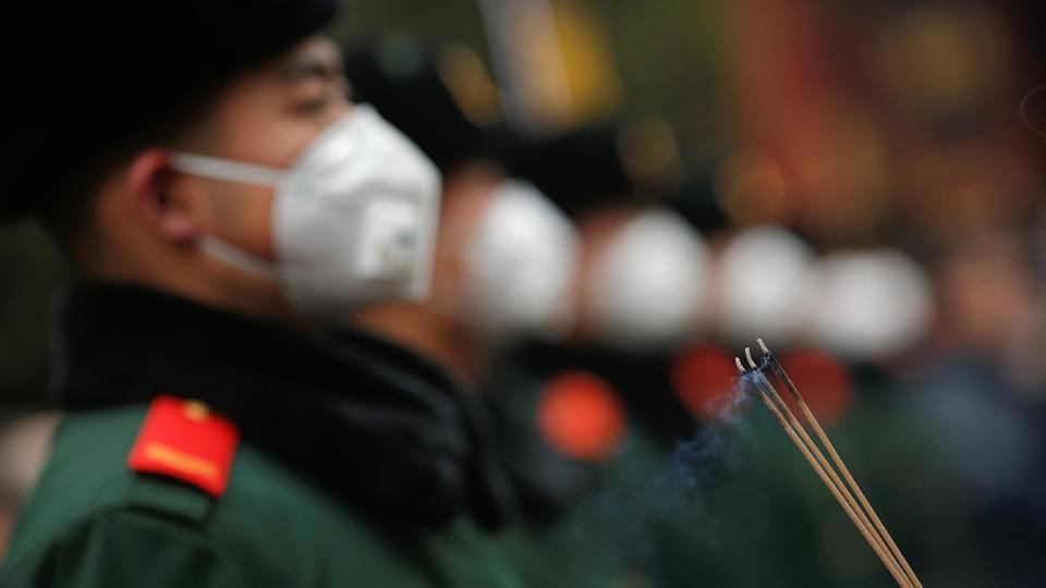 A woman holds incense sticks in front of paramilitary policemen providing security as people gather at Yonghegong Lama Temple to pray for good fortune on the first day of the Lunar New Year of the Rooster in Beijing, China. (Damir Sagolj/REUTERS)