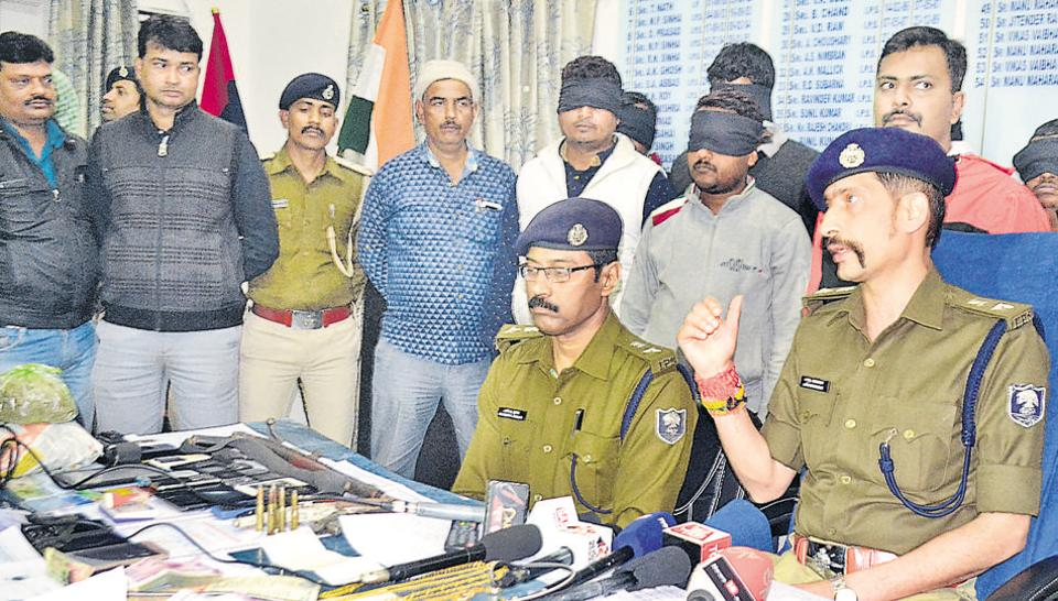 Patna  senior superintendent of police Manu Maharaaj (right) with the arrested army job racketeers (blindfolded in the background) in Patna.