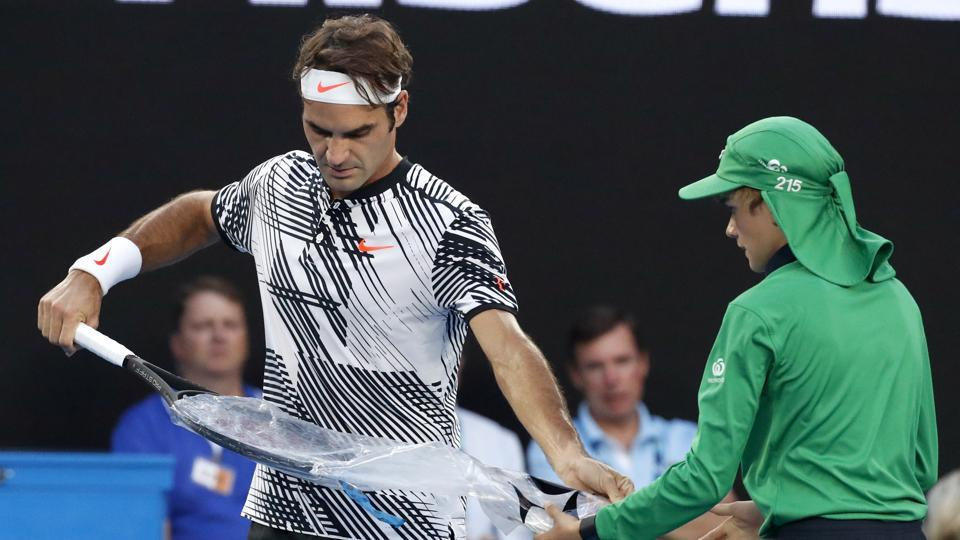 Roger Federer unwraps a new racket during the Australian Open final on Sunday. (AP)