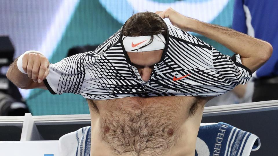 Roger Federer changes shirt during a break in his final against Rafael Nadal on Sunday. (AP)