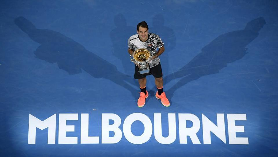 Roger Federer poses with the trophy after it was all over, in Melbourne on Sunday. (AP)