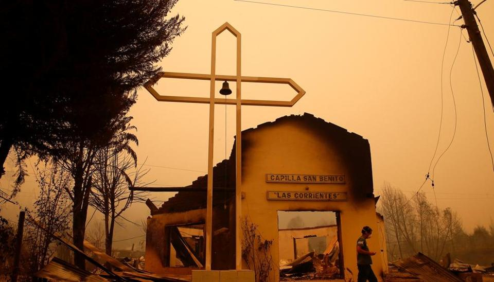 A man walks among the remains of a burnt church after a wildfire at the country's central-south regions, in Santa Olga, Chile, January 26, 2017. (Rodrigo Garrido / REUTERS)
