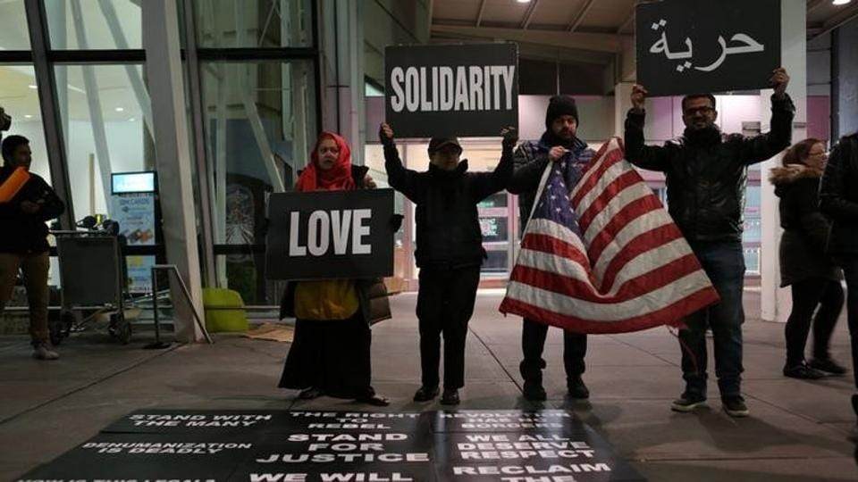 Protesters hold signs in opposition to U.S. President Donald Trump's ban on immigration and travel outside Terminal 4 at JFK airport in Queens, New York City.