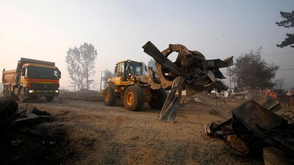 A bulldozer remove the remains of burnt houses after a wildfire at the country's central-south regions, in Santa Olga, Chile January 28, 2017.  (Carlos Vera / REUTERS)