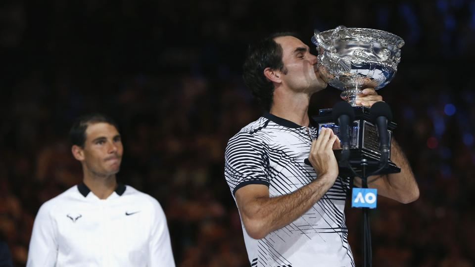 Roger Federer kisses the trophy as Rafael Nadal looks on.  (REUTERS)