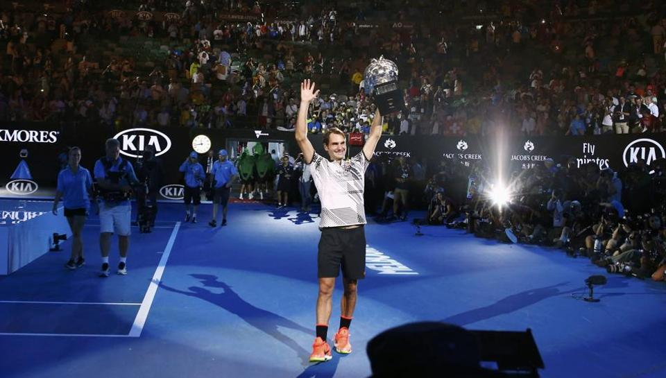 Roger Federer holds up the trophy for the crowd at Melbourne Park, on Sunday.  (REUTERS)