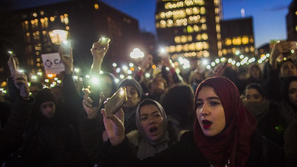 Muslim women shout slogans during a rally against President Donald Trump's order cracking down on immigrants living in the US at Washington Square Park in New York on Wednesday.