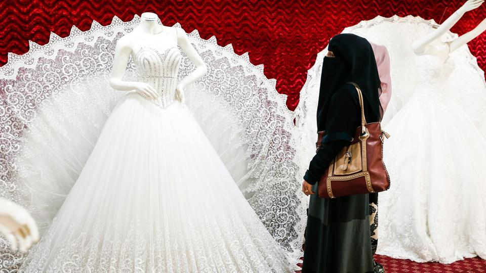 Two Yemeni women, one clad in a burqa, browse through wedding dresses in a shop in the capital Sanaa on January 28, 2017. Despite the conflict in Yemen that led to the deterioration of the economic situation in the country, which was already struggling financially, people continue to spend on weddings and other celebrations.  (Mohammed HUWAIS / AFP)
