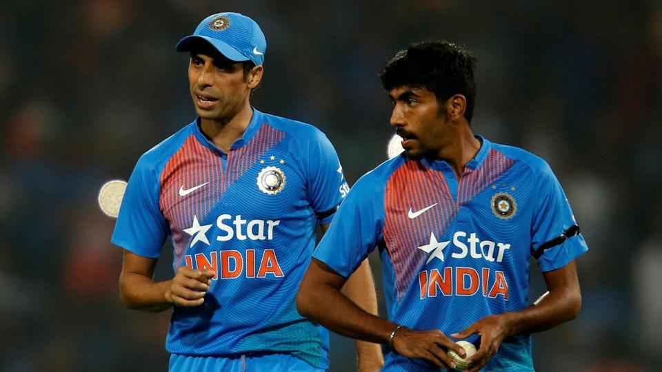 Ashish Nehra (L) and Jasprit Bumrah speak during the T20 match against England in Nagpur.