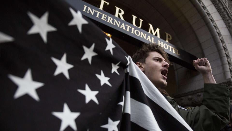 John Alfonso holds a black and white American flag during a protest in front of the Trump International Hotel Washington in Washington, DC.  (Zach Gibson/AFP)