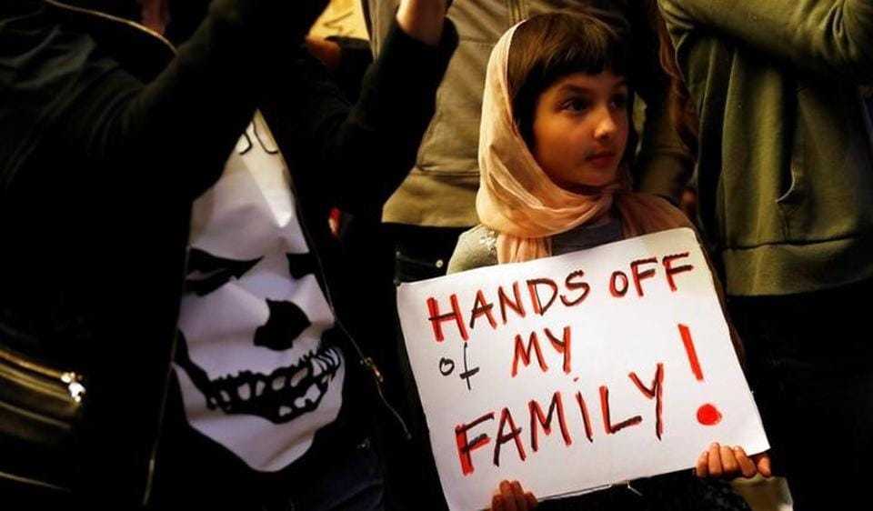 Rosalie Gurna, 9, holds a sign in support of Muslim family members as people protest against US President Donald Trump's travel ban on Muslim majority countries at the International terminal at Los Angeles International Airport, California, January 28, 2017