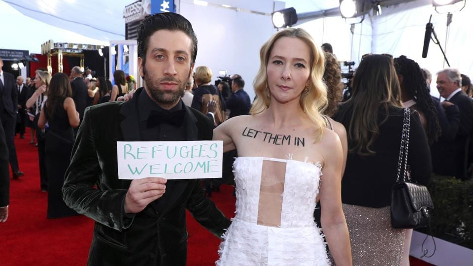 Simon Helberg  and Jocelyn Towne display protest signs against the US policy of temporarily barring refugees and citizens of seven predominantly Muslim countries, at the 23rd annual Screen Actors Guild Awards at the Shrine Auditorium & Expo Hall, in Los Angeles.  (Matt Sayles/Invision/AP)