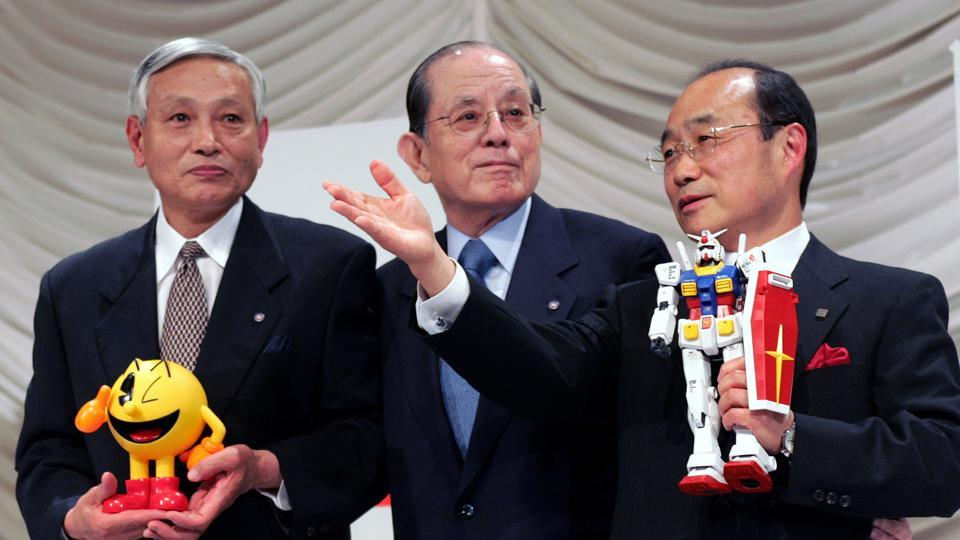 Japanese toy maker Bandai Co President Takeo Takasu (R), holding the company's