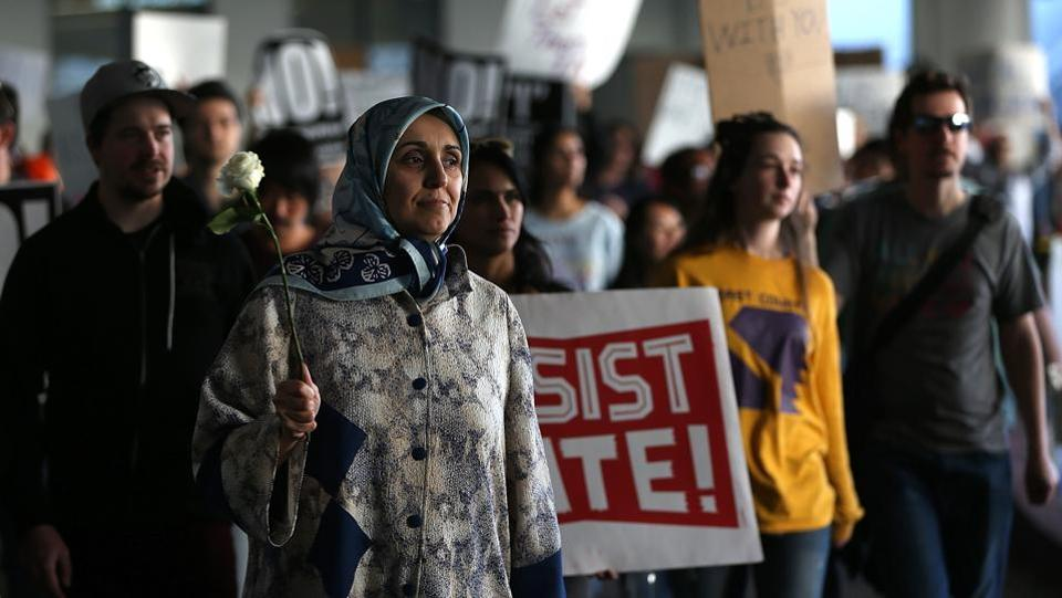 Protesters hold signs as the march during a demonstration against the immigration ban that was imposed by US President Donald Trump at Los Angeles International Airport. (Justin Sullivan/AFP)