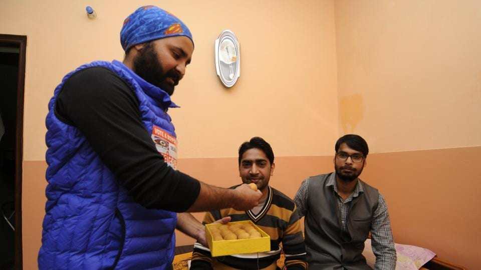 Manveer's brothers and his friend Ravindra celebrate his victory by sharing sweets.