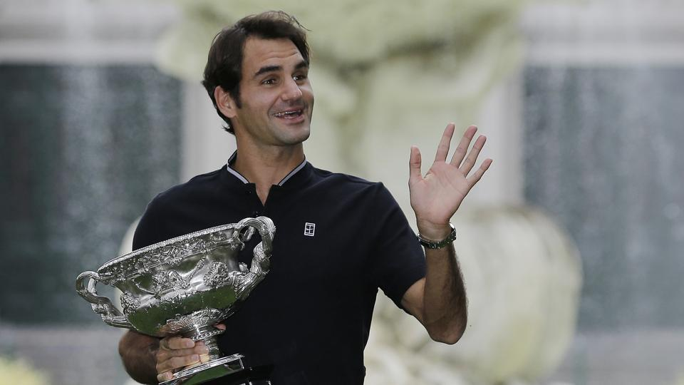 Roger Federer waves to fans as he holds his Australian Open trophy at Carlton Gardens in Melbourne on Monday.