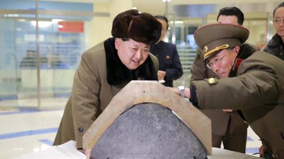 North Korean leader Kim Jong Un looks at a rocket warhead tip after a simulated test of atmospheric re-entry of a ballistic missile, at an unidentified location in this undated photo released by North Korea's Korean Central News Agency (KCNA) in Pyongyang.