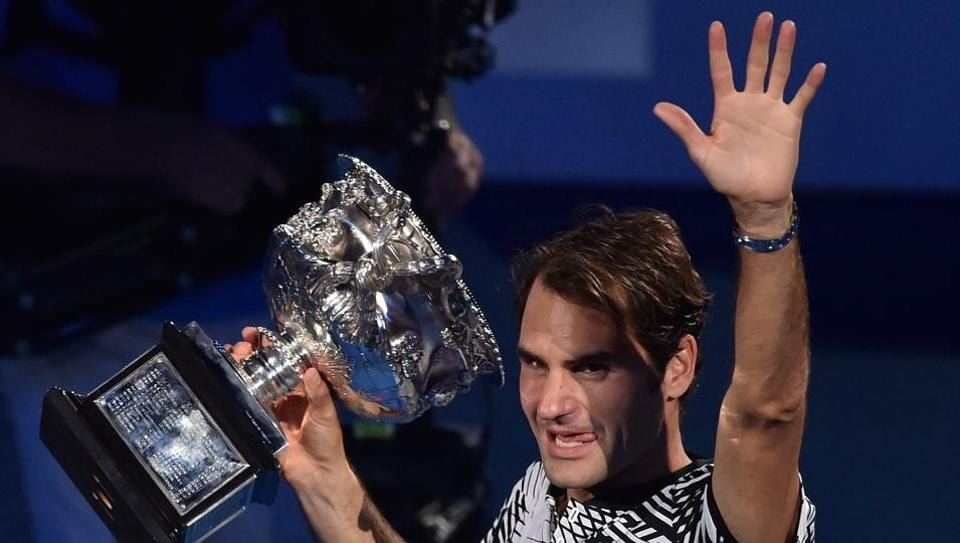 Roger Federer holds the winner's trophy during a victory lap following his win over Rafael Nadal in the Australian Open final.