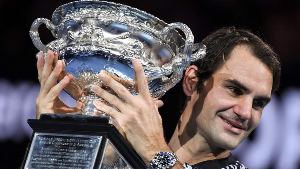 Switzerland's Roger Federer celebrates with the championship trophy during the Australian Open awards ceremony after his victory against Rafael Nadal.