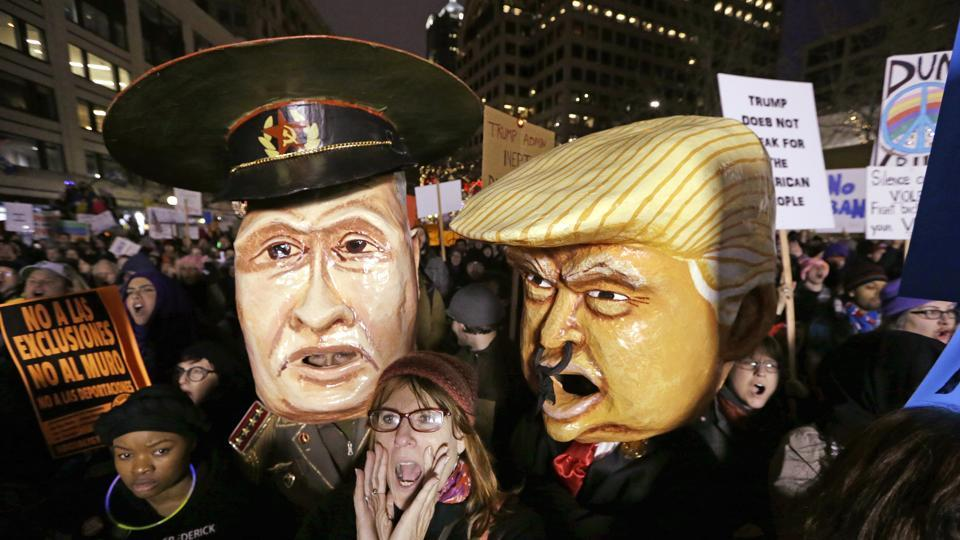 A woman shouts out as she stands in front of effigies portraying Russia's President Vladimir Putin and US President Donald Trump at a rally in Seattle to oppose Trump's executive order banning travel to the US by citizens of several countries .