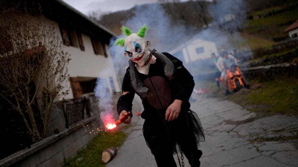 A masked reveller holds a flare during celebrations in Ituren.  (Reuters photo)