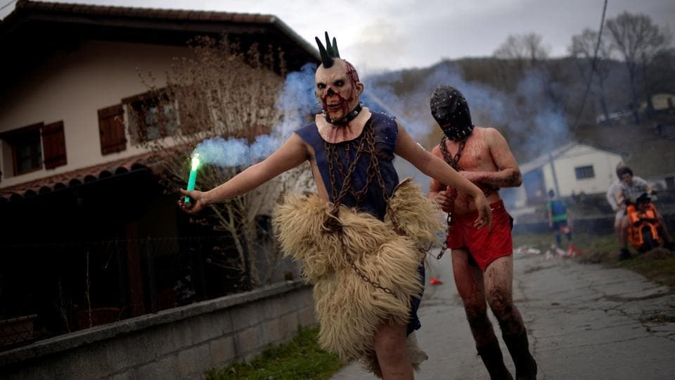 A masked reveller holds a flare during carnival celebrations in Ituren.  (Reuters photo)