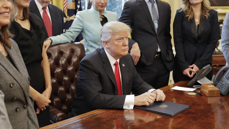 President Donald Trump surrounded by small business leaders poses signing an executive order in the Oval Office of the White House in Washington on Monday.
