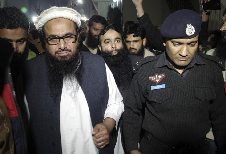A Pakistani police officer escorts Hafiz Saeed, left, Chief of Pakistan's religious group Jamaat-ud-Dawa outside party's headquarters in Lahore, Pakistan, Monday, Jan. 30, 2017. Pakistan has placed the leader of a charity linked to a militant group under house arrest. Hafiz Saeed, whose Jamaat-ud-Dawa is a front for Lashkar-e-Taiba, the group behind the 2008 Mumbai attacks, was placed under house arrest along with four aides. (AP Photo/K.M. Chaudary)