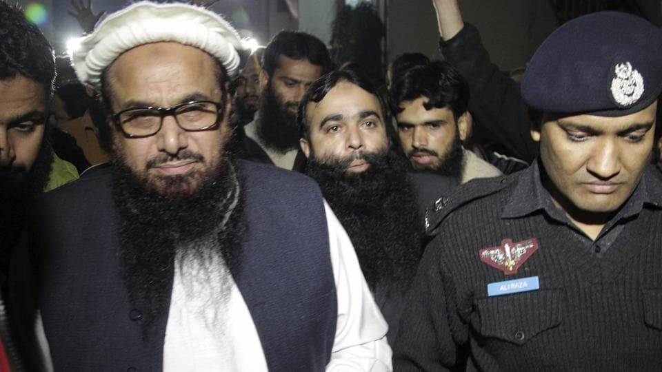 A Pakistani police officer escorts Hafiz Saeed, left, chief of Pakistan's religious group Jamaat-ud-Dawah outside party's headquarters in Lahore, Pakistan, Monday, Jan. 30, 2017.