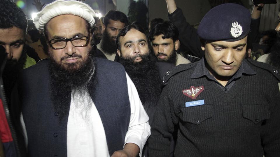 A Pakistani police officer escorts Hafiz Saeed in Lahore on Monday.