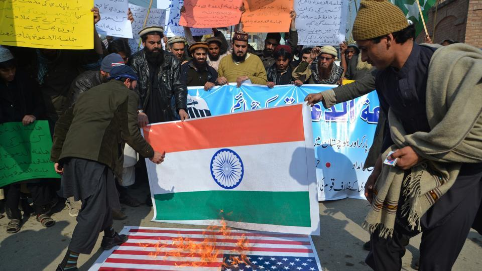 Supporters of Hafiz Saeed, head of the Pakistani religious charity, Jamaat-ud-Dawa, burn representations of US and Indian flags, to condemn his arrest, during a rally in Peshawar on Tuesday.